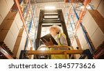 Small photo of Professional Female Worker Wearing Hard Hat Lifts Herself on Aerial Work Platform to Check Stock and Inventory with Digital Tablet on the Higher Level of Retail Warehouse full of Shelves with Goods