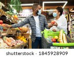 Small photo of Grocery Shopping. African Family Couple In Masks Buying Vegetables Together Standing With Shop Cart In Supermarket Groceries Store Indoor. Buyers Choosing Healthy Food Concept