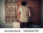 Small photo of A peeping tom is looking out through his blinds