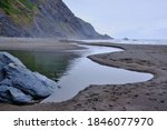 Small photo of River empties to the sea across the sand at Humbug Mountain State Park, Oregon on a foggy, June morning