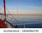 A sailboat motors at sunset along the coastline of British-Columbia