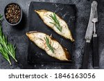 Baked halibut fish steak. Black background. Top view