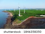 Small photo of Aerial view of giant wind turbines standing in the green field by the beach in a seaside park along the beautiful coastline on a sunny summer day, in Zhongtun, Baisha Township, Penghu County, Taiwan