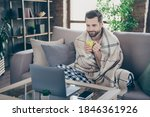 Small photo of Photo of handsome homey guy sit comfy sofa saturday weekend drink fresh coffee watch film notebook stay home quarantine pajama covered checkered blanket living room indoors