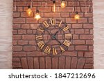 Large classic Clock with roman numerals on a red brick wall. Vintage Clock on wall with glowing garland. Interior concept. Metal wall clock on the background of grunge wall in the Loft apartment.