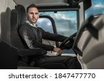 Caucasian Coach Bus Driver in His 40s Behind Modern Bus Vehicle. Public Transportation Work. - stock photo