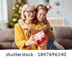 Small photo of Happy family on Christmas morning. Affectionate grandmother and cheerful granddaughter open a holiday gift together at home