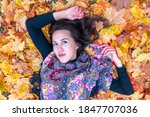 Young Woman Lies On Autumn...