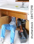 Man with body half under sink cabinet and reaching for wrench in toolbox. Home repair concept. - stock photo