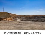 Small photo of Copper ore open-pit mining. Quarry panorama. Electric mast and quarry machine on blue sky background.