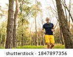 Small photo of Merry grizzled bearded fit male is doing cardio workout in nature and going jogging among trees