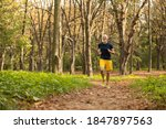 Small photo of Happy fit mature grizzled man is running alone through green sunny forest during workout outdoors
