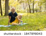 Small photo of Happy fit grizzled man is having fun while drinking water after training in sunny forest