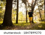 Small photo of Happy grizzled man is starting morning with going jogging in nature and listening to music