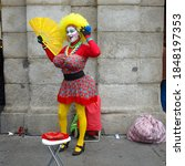 Small photo of Madrid, Spain. 12/05/2009. Mime disguised as a voluptuous woman with colorful clothes doing her show in a street of Madrid.
