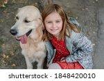 Little Girl Hugging Golden...