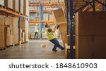 Small photo of Shot of a Warehouse Worker Has Work Related Accident. He is Falling Down BeforeTrying to Pick Up Heavy Cardboard Box from the Shelf. Hard Injury at Work.
