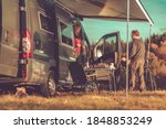 Caucasian Couple and Their Weekend Getaway. Camper Van RV Boondocking in Remote Place During Scenic Fall Foliage. Class B Motorhome RVing Theme. - stock photo