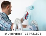 repair, building and home concept - close up of male in gloves holding painting roller - stock photo