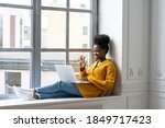 Small photo of Smiling African American millennial woman with afro hairstyle in yellow cardigan sitting on windowsill, resting, looking at camera webcam, say hello, talking on video chat with her friends on laptop.