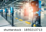 Small photo of Blurred electric car charging station for charge EV battery. Plug for vehicle with electric engine. EV charger. Clean energy. Charging point at car parking lot. Future transport technology.