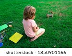 Child Pupil Sitting On Lawn In...