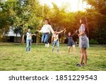 Small photo of Happy Indian asian young friends playing together with jumping rope outdoors. People playing skipping rope games and laughing outdoors. Happy man or woman jumping over skipping rope held by others