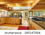 Stock photo view of kitchen cabinets ceiling beams and hardwood floor with red rug 185147006