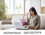 Small photo of Happy indian woman student, winner celebrating achievement, online bid win, victory, success raising hand in yes gesture looking at laptop feeling glad receiving discount voucher on email at home.