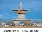 A large Inukshuk that sits on the shoreline of Hudson Bay in Churchill, Manitoba in northern Canada. Icy sea ice in the background and blue sky with clouds.