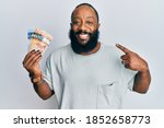 Young african american man holding canadian dollars smiling happy pointing with hand and finger