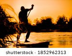 A Young Man Rowing On A Sup...