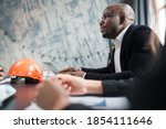 A man african american director of a construction company holds a meeting with colleagues, sits at a table with documents and an orange construction helmet - stock photo