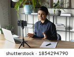 Small photo of Successful Indian businesswoman recording webinar, using smartphone on tripod, sitting at desk in office, smiling young employee business coach teacher influencer shooting video for blog, speaking
