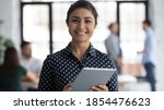 Small photo of Glad to help you! Portrait of smiling confident indian female insurance broker bank manager hr assistant standing in open space office holding digital tablet looking at camera ready to assist client