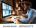 Small photo of Business man having virtual team meeting on video conference call using computer. Social distance worker working from home office talking to diverse colleagues in remote videoconference online chat.