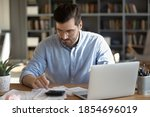 Small photo of Serious man in glasses sit at workplace desk in office use calculator calculates monthly expenses, taxes, check bank account balance, summarize total sum. Family or personal budget management concept