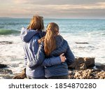 Mother and daughter holding each other and looking at ocean landscape. West coast of Ireland. Concept family, mother and daughter relationship.