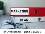 Small photo of Red and white folders with documents lying on the desktop next to a calculator and a pen. The lettering on the folder has financial or marketing significance. Business concept.