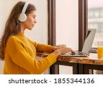Small photo of Nice beautiful female with blonde long hair working on laptop sitting at home. Online shoping, alternative office freelance, gig economy, digital nomad