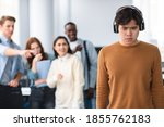 Small photo of Bullying Concept. Rude diverse group of people mocking and making fun of sad asian guy wearing headphones, pointing fingers at him and laughing, standing in blurred background. Prank and abuse