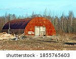 Small photo of View of an old, rusty, abandoned hangar. An image of decrepitude or a natural disaster.