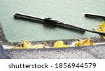 Frozen windshield wipers. The car is covered with ice, Icing.Change of weather. Autumn leaves are covered with ice and snow on the car windshield. Hydrometeorological Center. Bad weather conditions.  - stock photo