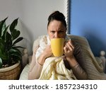 Small photo of A sick woman in a knitted scarf and on the bed, drinking medicine, wincing. Wrinkles on the face, old age. Treatment, malaise, cold. A yellow mug in his hand. Bed rest, isolation.
