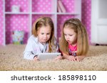 cute girls playing on a tablet... | Shutterstock . vector #185898110