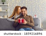 Small photo of Young red-haired woman from behind hugs and kisses her beloved husband giving him a gift on this special day. Concept of gifts for birthdays, Christmas, Valentine's Day and Men's Day.