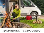 Single Caucasian Woman in Her 30s with RV Camper Van Motorhome, Camping Alone and Preparing Food on Campfire. Campsite and Vacation Theme. - stock photo