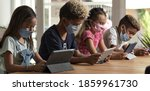 Small photo of Banner four children wear facemasks sit at table use wireless gadgets ignoring each other prefer internet games and virtual communication. Alpha generation, modern technology overuse, phubbing concept