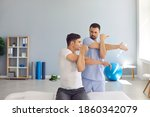 Small photo of Joint motion recovery. Physiotherapist teaching male patient to do arm across chest or cross-body stretch exercise to relieve shoulder pain, cure frozen shoulder and help get rid of joint stiffness