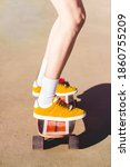 Small photo of Legs of a woman riding a skateboard. Skater outfit. California concept. Cool Girl wearing shorts at the beach with a longboard. Skate surf